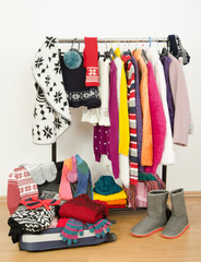 Wardrobe with winter clothes arranged on rack and a full luggage