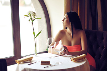 Beautiful young woman sitting at the table alone in a restaurant