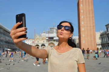 A beautiful young woman taking herself a selfie in Venice
