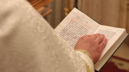 hands of praying priest on the Bible 1080p