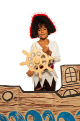 Little boy playing being pirate on cardboard ship