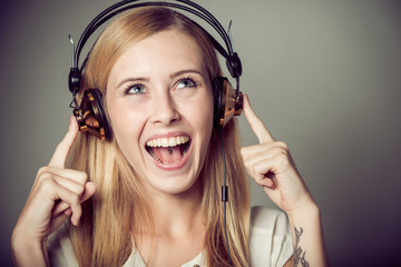 young blonde woman enjoying music on headphones