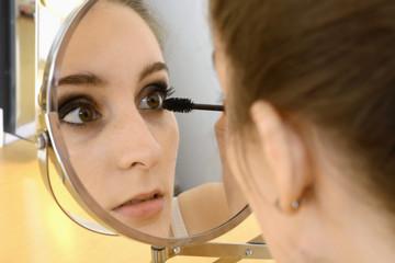 Twen trägt Wimperntusche und Eyeliner auf