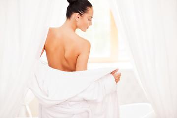 Taking off her bathrobe.