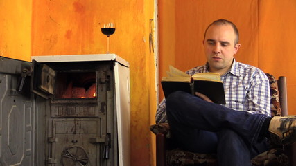 man read book sip wine next to ancient smoldering fire stove