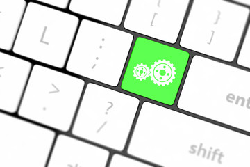 cogwheel gear mechanism on button on white computer keyboard.