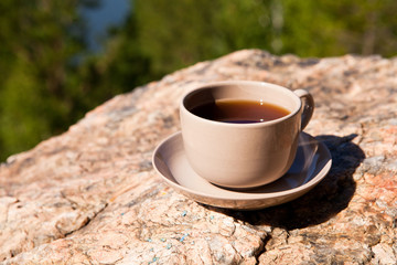 Cup on big stone over nature background