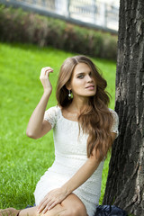 Young pretty girl sitting on green grass