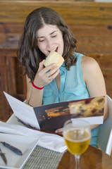 Woman reading restaurant card and eating bread