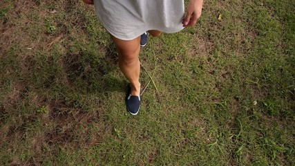 Young Female Legs Walking on the Grass. Slow Motion.