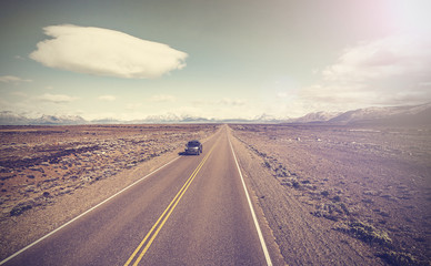 Vintage picture of car on endless country highway, Ruta 40.