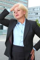 Geschaeftsfrau gestresst mit Hand an der Stirn