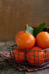 Ripe tangerine fruits in wire basket with copy space