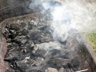 Smoking burning charcoal on barbecue
