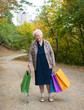 Old woman standing with shopping bags