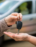 Fototapety Woman giving keys from a car to another woman