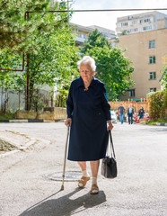 Old woman walking with a cane