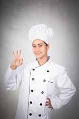 young woman chef showing ok