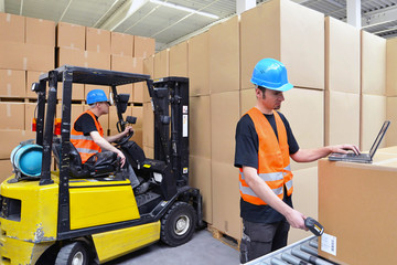 Arbeiter scannt Kiste im Warenlager // Workers in logistics