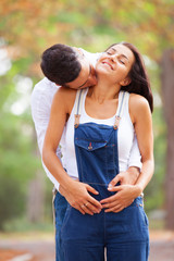 Teen couple kissing in the park in autumn time