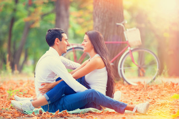 Teen couple with bike in the park in autumn time