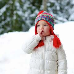 Little girl in warm outfit playing outdoors in winter