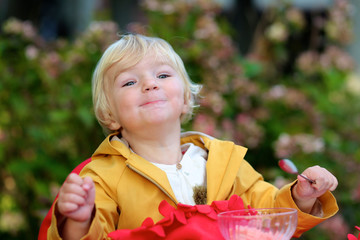 Little girl eating yoghurt in outdoors cafe