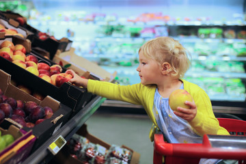 Little girl doing shopping in supermarket