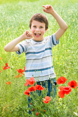 boy in red flower poppy meadow have fun