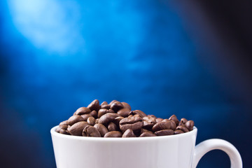 Coffe white mug filled with seeds on black and blue background.