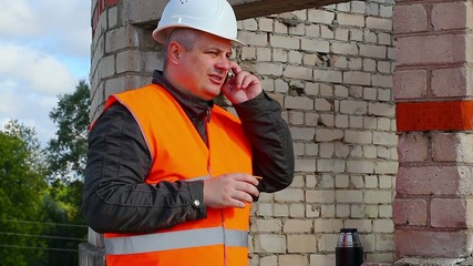 Construction Engineer with cup of coffee and cell phone