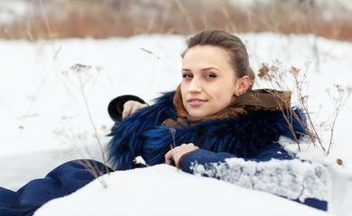 woman lying in coat on  snow