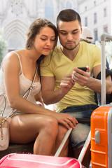 Couple with GPS navigator and baggage