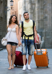 Man and woman in shorts walking through city