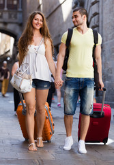 Young couple in shorts walking through city