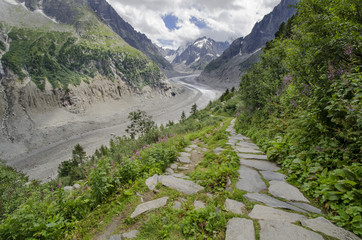 Alpine landscape with path, mountains and glacier