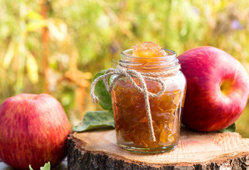 Jar of apple preserves on grass background