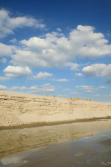 Sand quarry, heap of sand and puddle, beautiful landscape