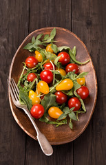 Red and yellow tomatoes with herbs and fork