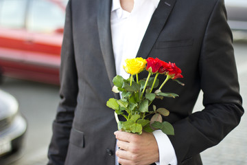 Brutal man in a black suit  with a bouquet of roses in hands