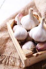 Fresh garlic in box, on wooden background