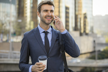 Business man talking on a cell phone smiling downtown