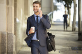 Attractive commuter walking downtown with coffee and briefcase