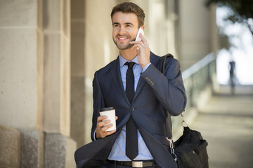 Businessman walking with coffee and briefcase on the phone