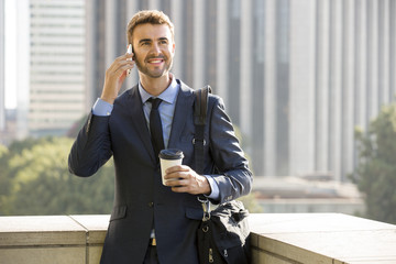 Businessman standing outside the office on the phone with coffee