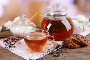Teapot and cup of tea on table on light background