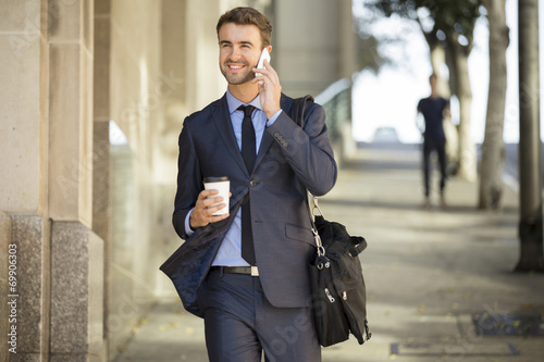 Attractive commuter walking downtown with coffee and briefcase - 69906303