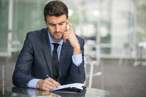 Focused businessman thinking and writing outside office - 69906525