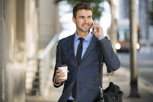 Commuter waiting for the bus with coffee using his cell