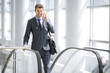 Businessman on the phone smiling at the escalator - 69907188